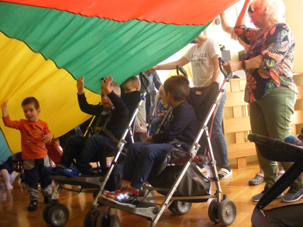 Dzieci bawią się pod kolorową chustą